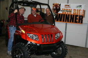 "Drew Taylor (L) and John Myers (R) of H.J. Baker's Tiger-Sul Products present Kevin Dockter (C) with a new Arctic Cat Prowler ATV as the Grand Prize winner of the ""Make Tracks Win Big"" sweepstakes."