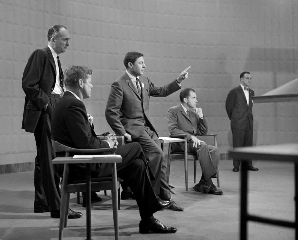 """During the 1960 debate, Kennedy proposed paying farmers an income that would equal their urban colleagues by imposing a system of mandatory production or marketing controls. His Republican opponent, Richard Nixon, thought the surplus would end in a few years and that farmers should """"operate in free markets with a minimum of [government] aid."""" Here, CBS News producer Don Hewitt (center) gestures while making arrangements for Kennedy and Nixon to speak in the first televised presidential debate. Photo: journalismprofessor.com"""