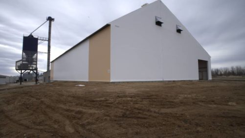 The building exterior features white fabric with tan trim.